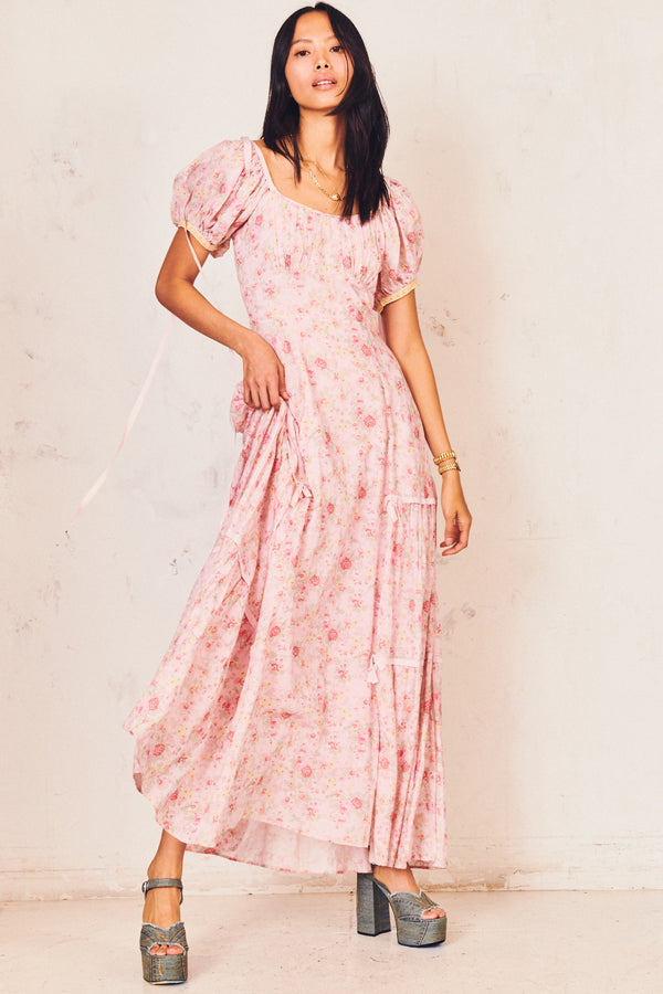 Pink floral maxi dress with front pocket detail and puffed short sleeves and bows at shoulders