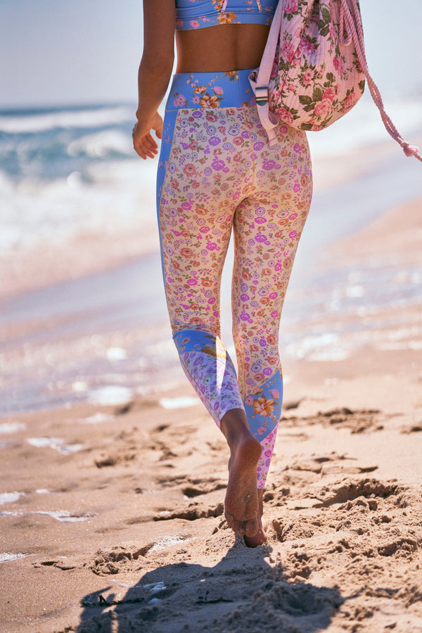 Pink, yellow, and blue floral print workout legging pants with wide waistband and tri tone calf detail