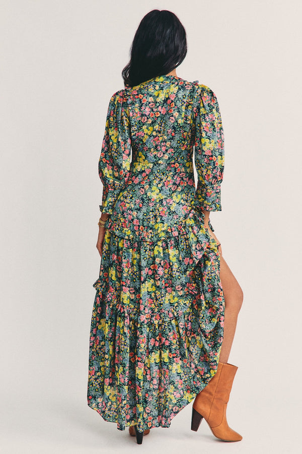 Green long sleeve maxi dress with multi colored floral pattern and tiered ruffle detail and v neck