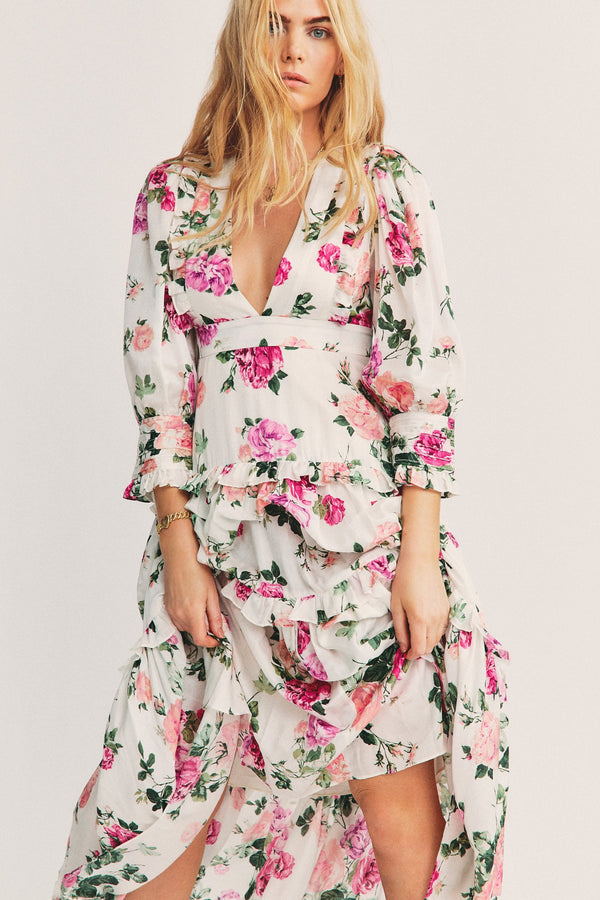 White long sleeve maxi dress with pink floral pattern and tiered ruffle detail and v neck