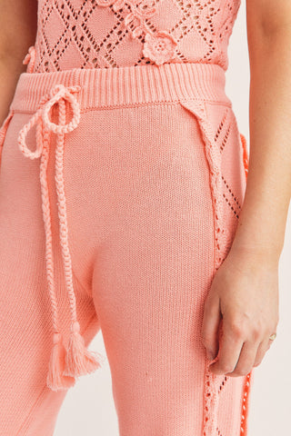 Peach colored knit jogger pants with pointelle detail on sides and tie waist with elastic ankle cuffs
