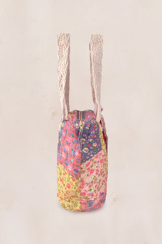 Multi-colored floral print duffle bag with braided macrame handles