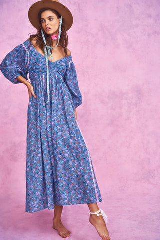 Blue floral print maxi dress with fitted waist and pink embroidery detail and deep V-neck and puffed long sleeves