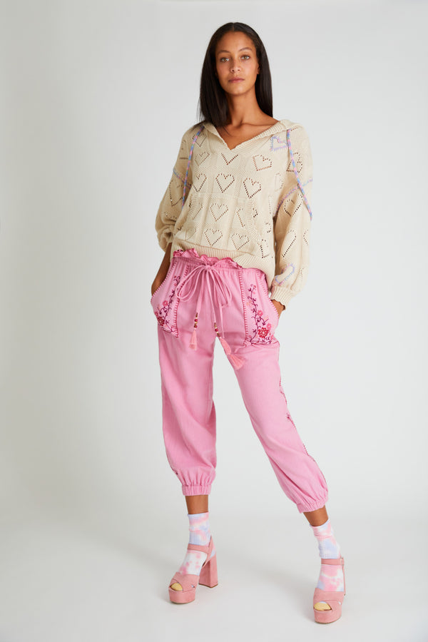 Pink jogger pant with cinched cuffs at the ankle. Adjustable tie waist and embroidery detail at the front pockets