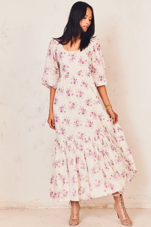 White maxi dress with purple floral print detailing and ruffled tiered skirt and puffed long sleeves