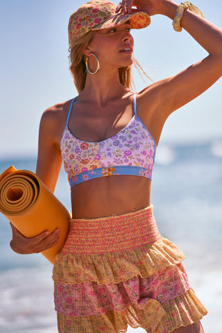 Pink, yellow, and blue floral print workout halter top with strappy criss cross back