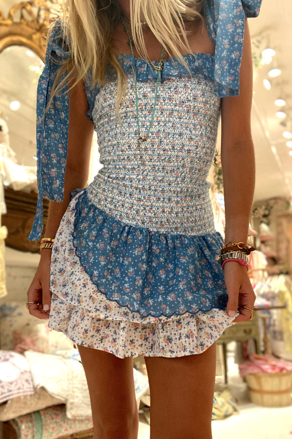 Blue and white floral print mini dress with smocked body detail and attachable bows at the shoulders
