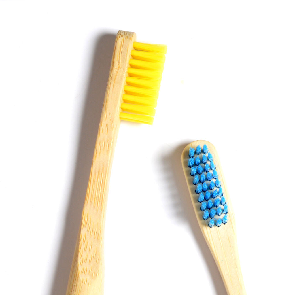 two Reco bamboo toothbrushes heads next to each other