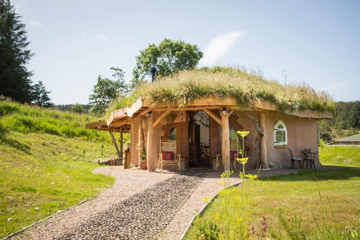 Eco retreats - Sustainable holiday accommodation - View of hobbit hideaway from outside with blue sky