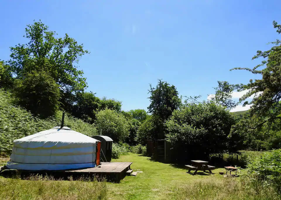 Eco retreats - Sustainable holiday accommodation - Moonlight Yurt in the middle of a green field with blue sky