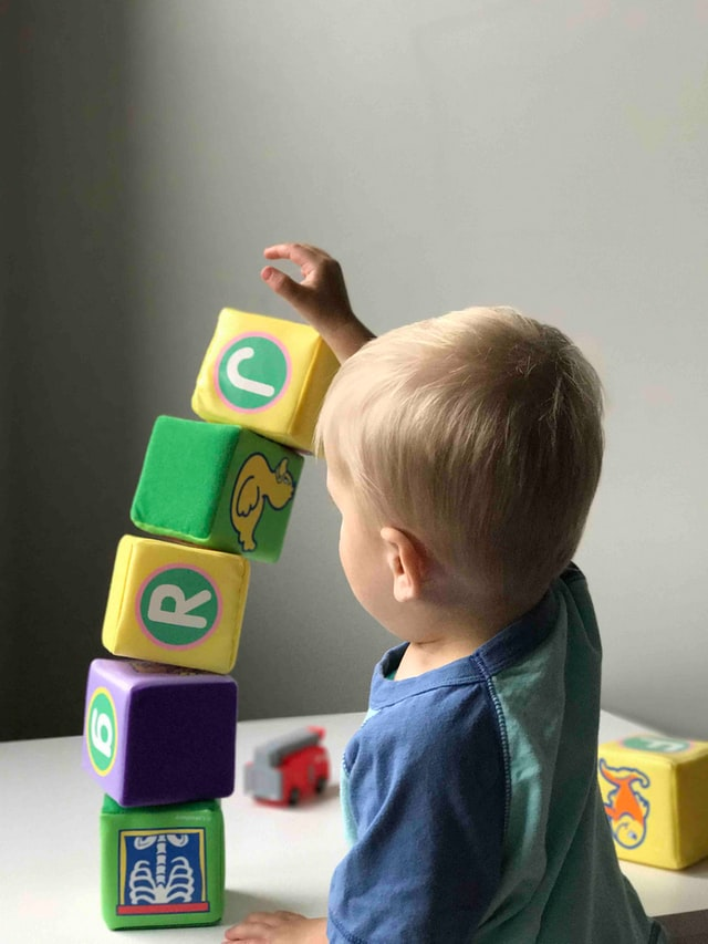 Toddler playing with to sustainable wooden blocks