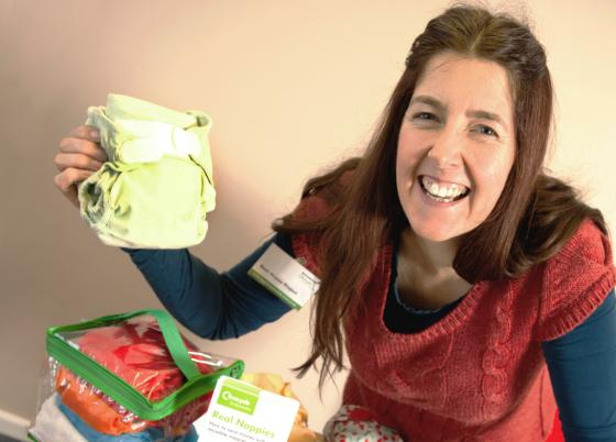 Woman holding up reusable eco-friendly nappy - source WRAP UK