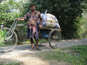 Man with tricycle transporting organic cotton reusable shopping bags from turtle bags