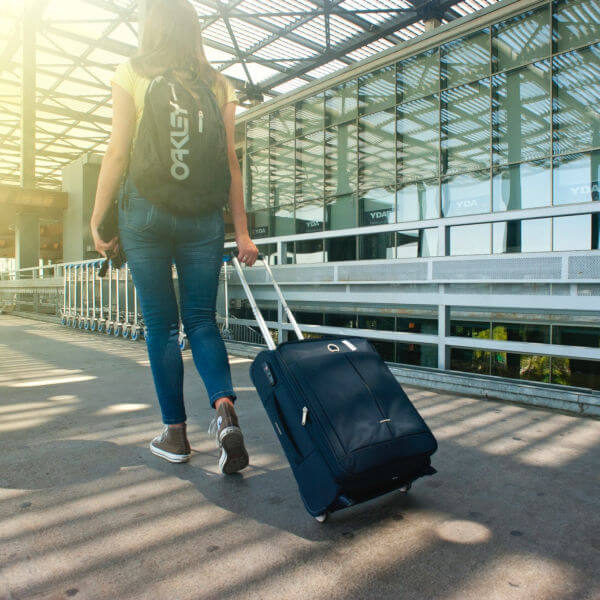 woman-walking-on-pathway-while-strolling-luggage