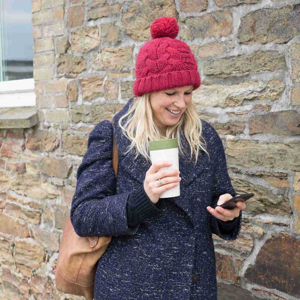 woman wearing blue coat and red hat walking with cream and green 12oz rcup recycled reusable coffee cup while on mobile phone