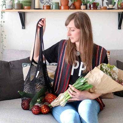 Black Organic Cotton String Shopping Bag Long Handle Turtle Bags with fruit and veg inside held by woman