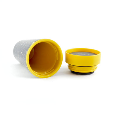 mustard and black rcup reusable coffee cup on its side with lid off