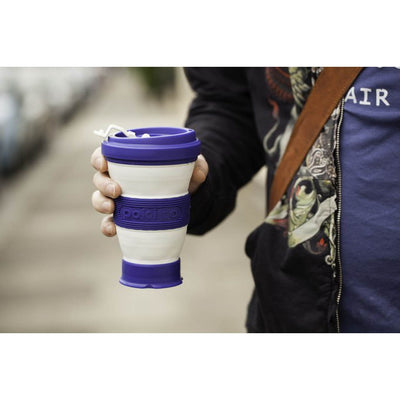 person holding grande blueberry pokito the collapsible coffee cup outside