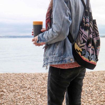 woman standing on beach holding black and mustard rcup recycled reusable coffee cup 12oz