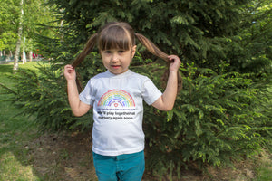 Girl wearing personalised Minimello Rainbow tshirt featuring names of children in her nursery class in support of the charity NHS Charities Together