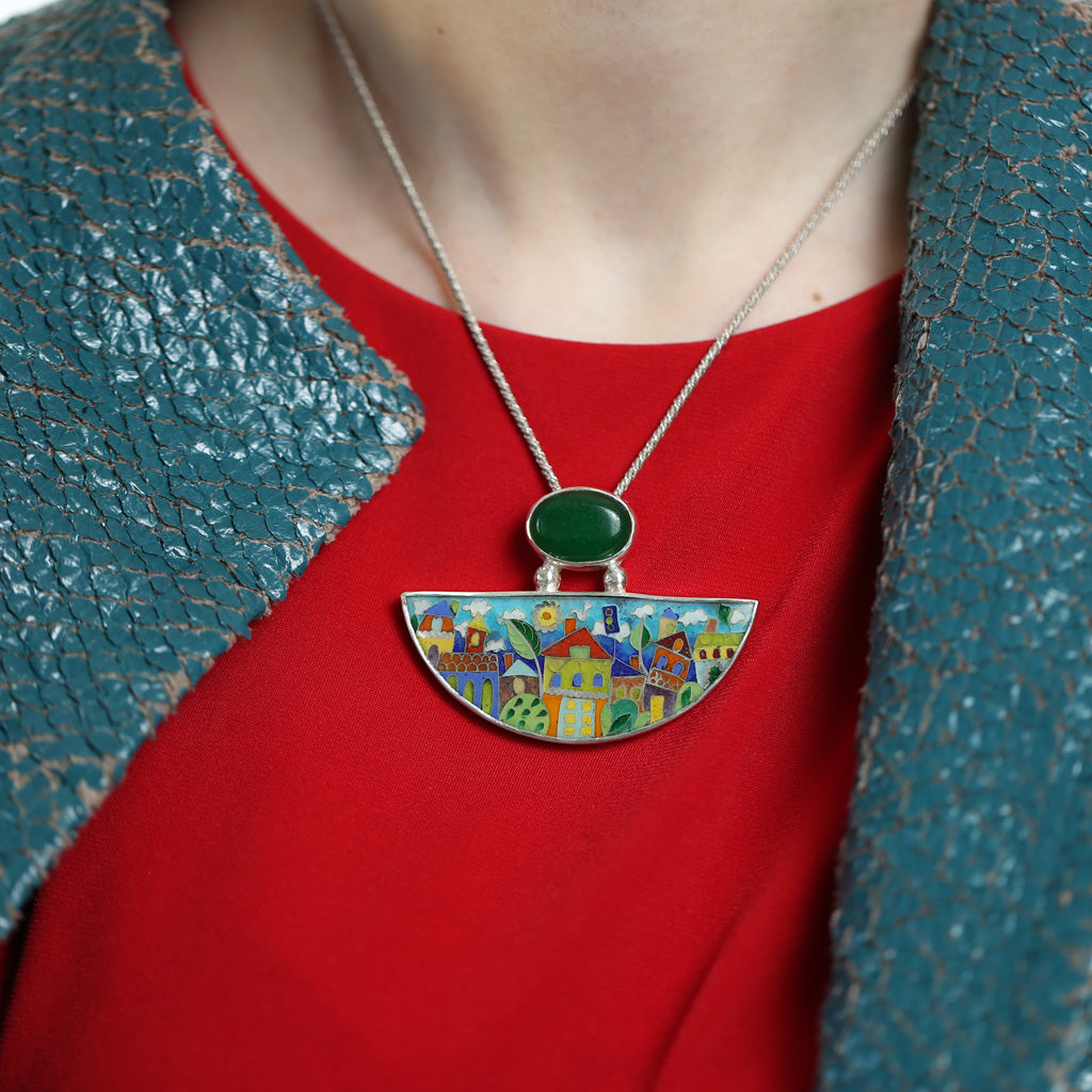 Handmade Enamel Pendant in shape of Half Moon with Natural Green Agata stone, beautiful enamel pattern inspired by picturesque Tbilisi buildings and streets. This pictures shows model's neckline wearing the necklace.