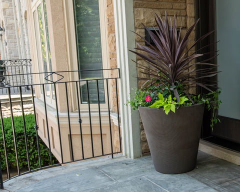 Self-watering planter filled with tropical plants on a balcony.