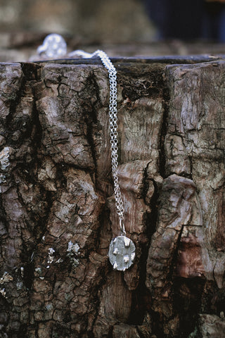 Close up of glacier jewellery melting on logs, contemporary silver necklaces with enamel, all handmade