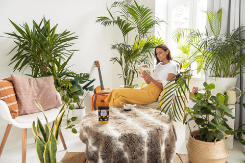 Woman surrounded by plants, reading a book and drinking CBD coffee