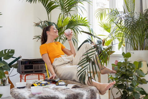 Woman smiling at home drinking CBD coffee and surrounded by plants""