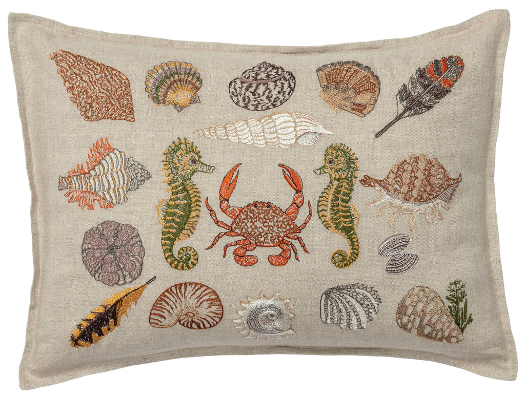 Decorative pillow embroidered with images of a seaside souvenir collection including different shells, feathers, sea horses and a crab in a colorful color palate.