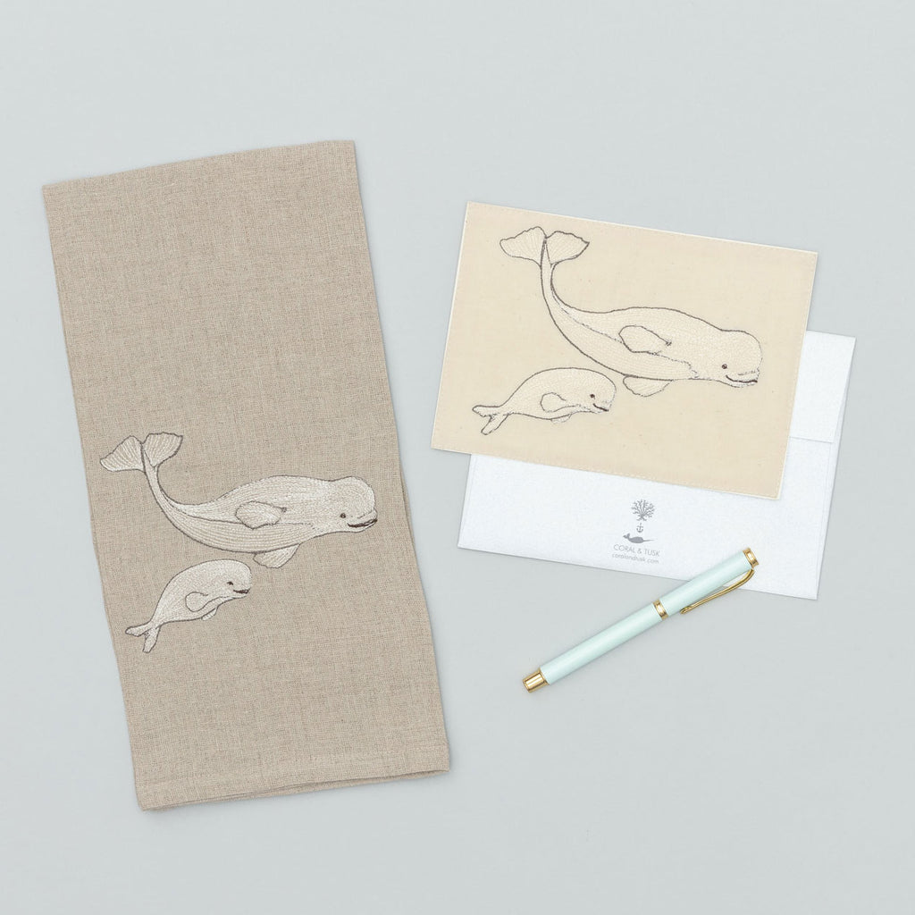 An embroidered linen tea towel and card featuring a mama beluga whale and her baby beluga whale.