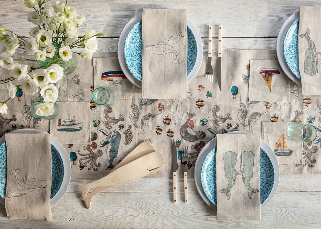 Overhead image of a set table with an embroidered table runner, dinner napkins and cocktail napkins featuring ocean animals including whales, fish, dolphin, narwhals, octopus, seals and turtles swimming.