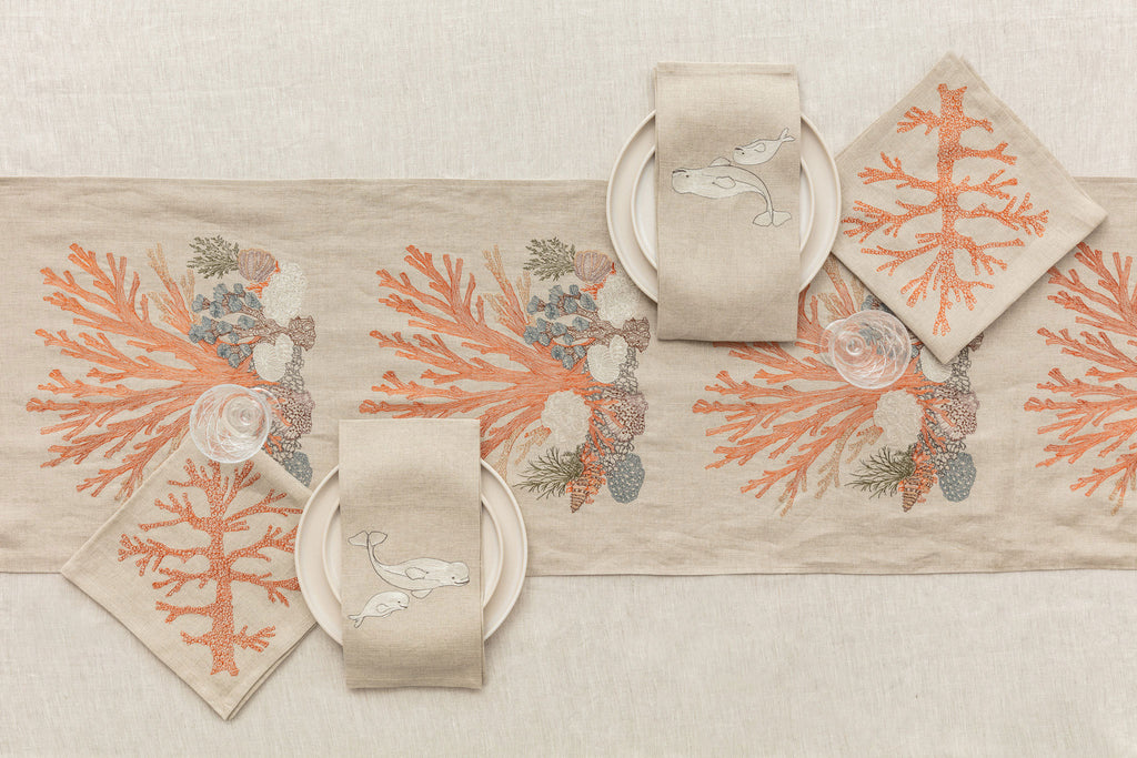 Embroidered table linen setting with coral designs and tea towels featuring a mama beluga whale and her baby beluga whale.