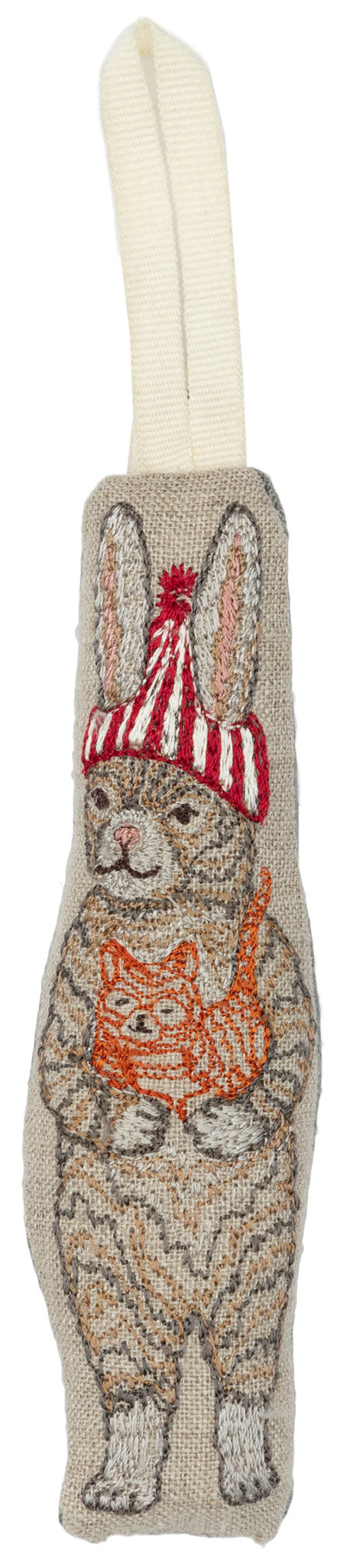 Embroidered and stuffed ornament depicting bunny with red striped beanie cap holding orange cat.