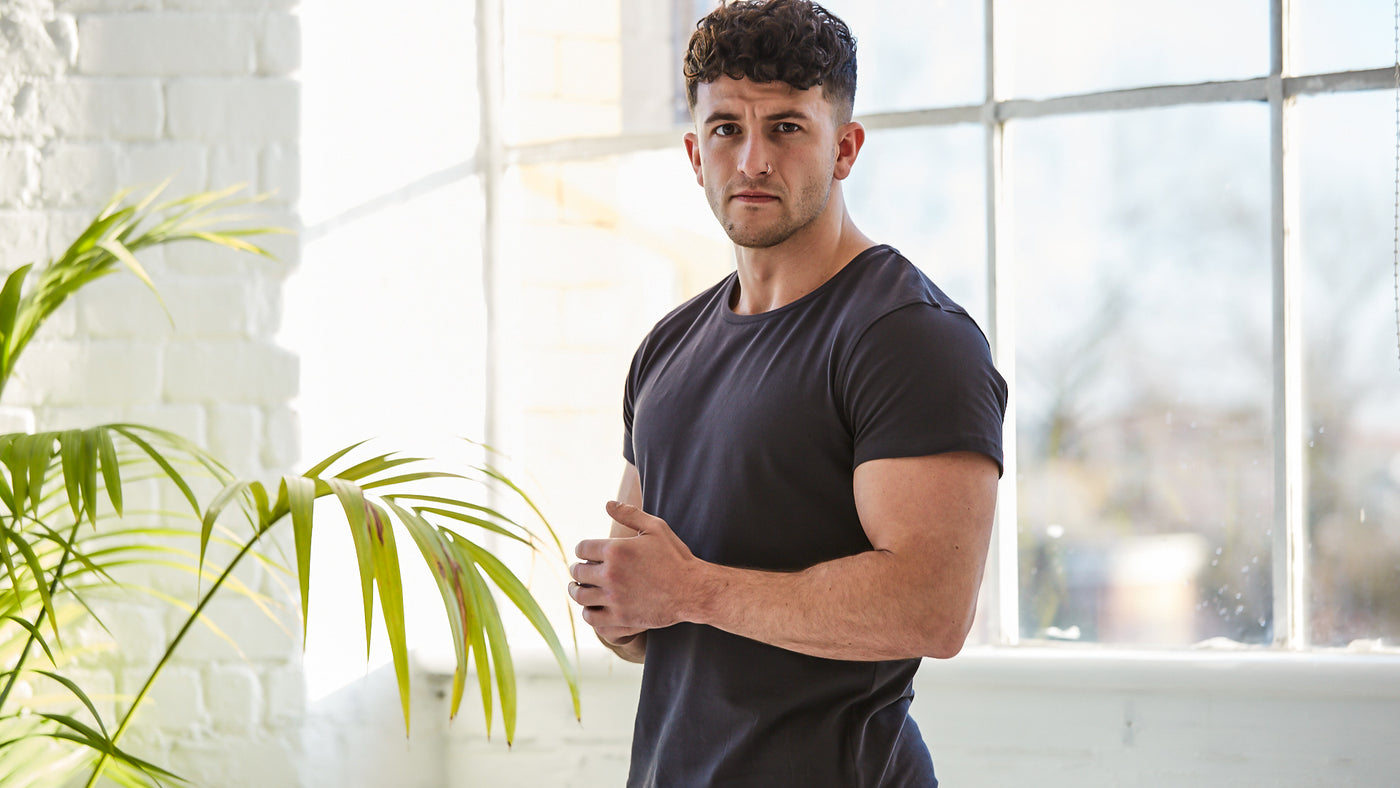 Man stood next to green plant in a bright room with natural light from window behind. He is wearing the short sleeved organic Brando t-shirt in colour Charcoal. Slim fitting t-shirt from Arbour Alexander.