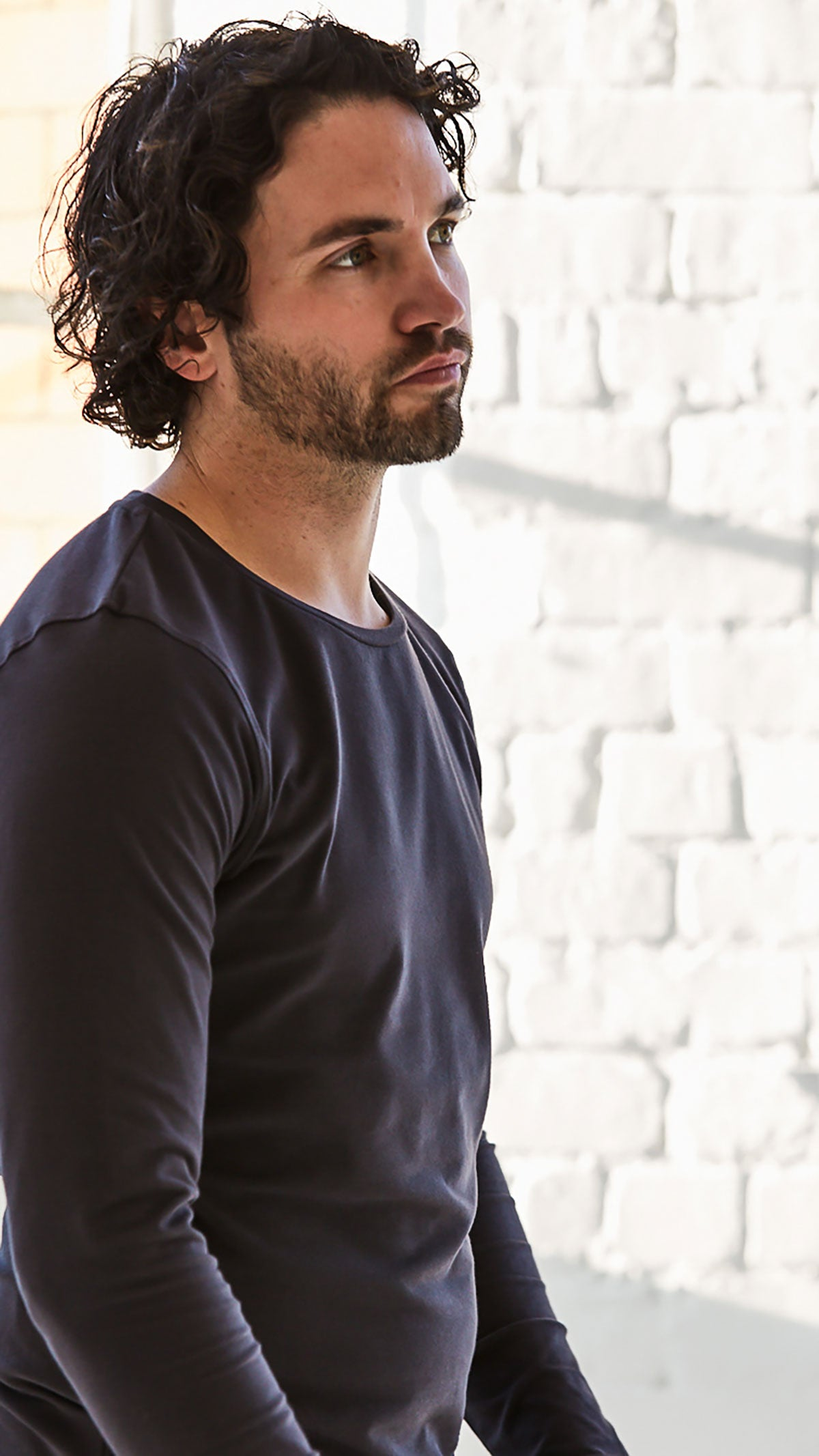 Man looking into the distance in a bright room with natural light from window. He is wearing a long sleeve organic Origin tee in colour charcoal. T-shirt is slim fitting from Arbour Alexander.