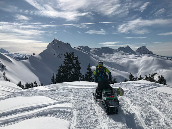 Snowboarding from a Snowmobile from mountain top with arctic cat