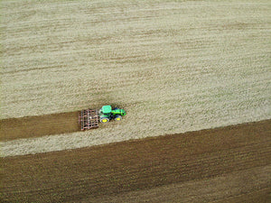 Farm Tractor Cutting Furrows In Field Aerial Image - Art Print