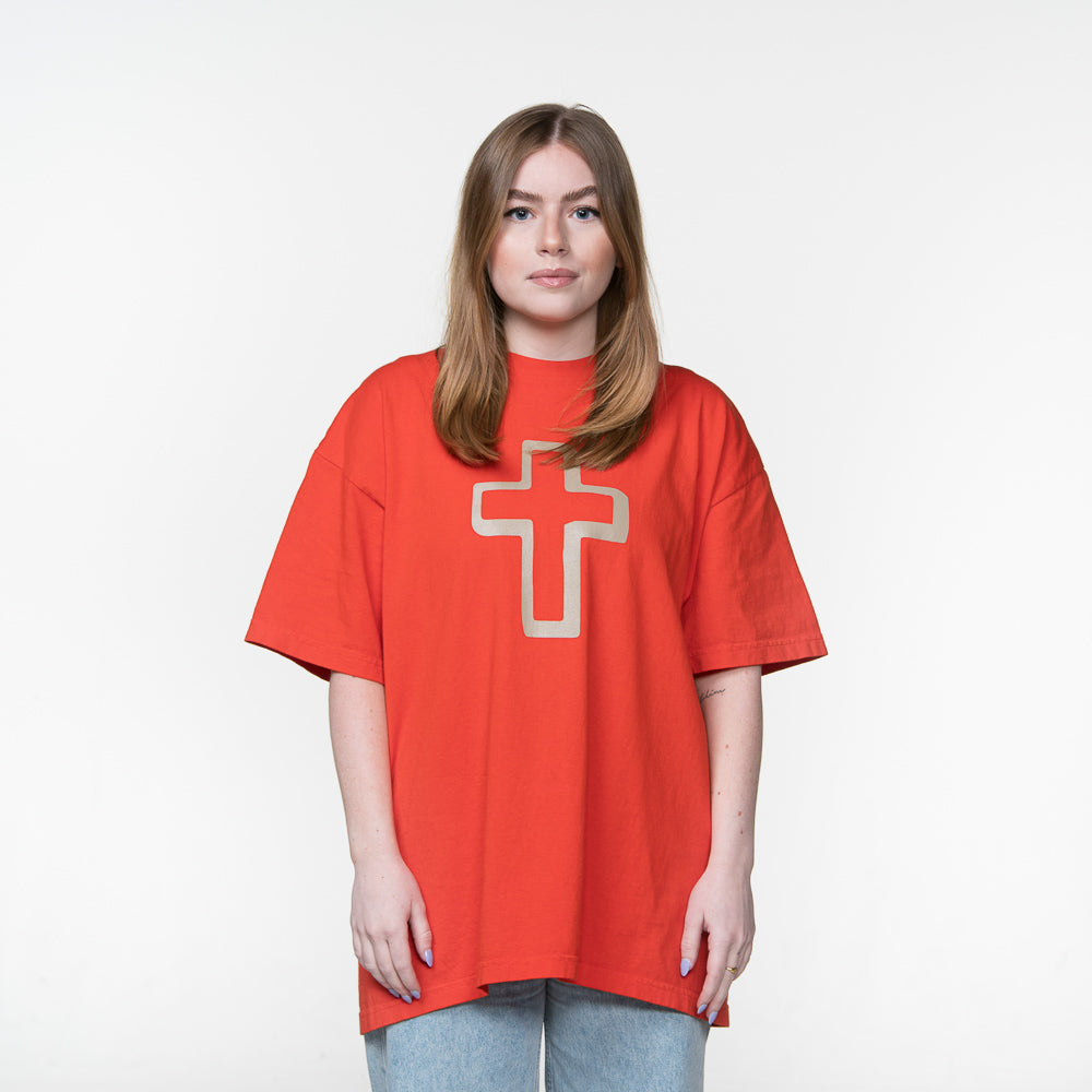 Front Facing - Caucasian female with large tan cross in center of orange shirt.