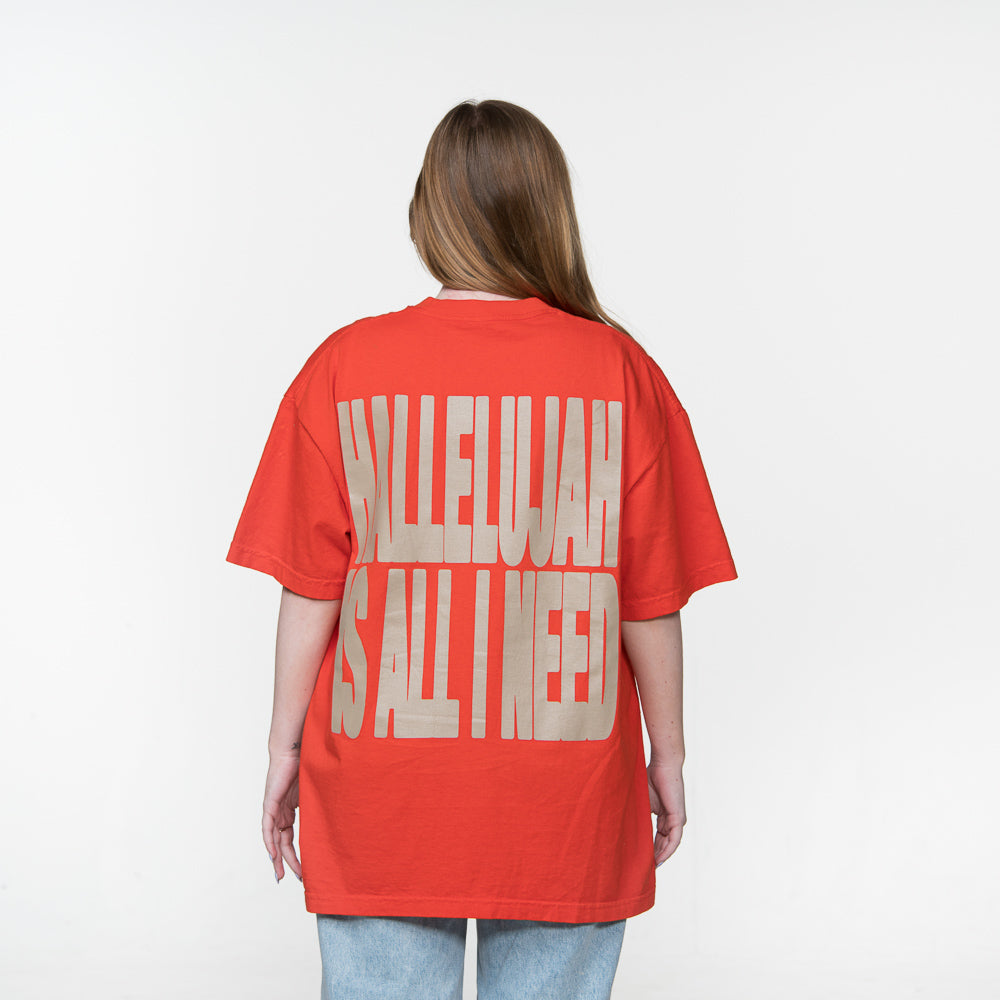 Back Facing - Caucasian female with Hallelujah Is All I Need in large tan font on the back of orange shirt.