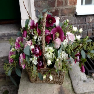 Funeral Basket of Spring Flowers Pinks and Purples.