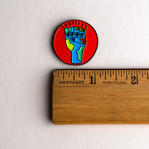 Zero Hour Earth Fist pin with ruler for scale