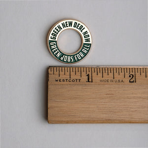 Green New Deal enamel lapel pin and ruler for scale