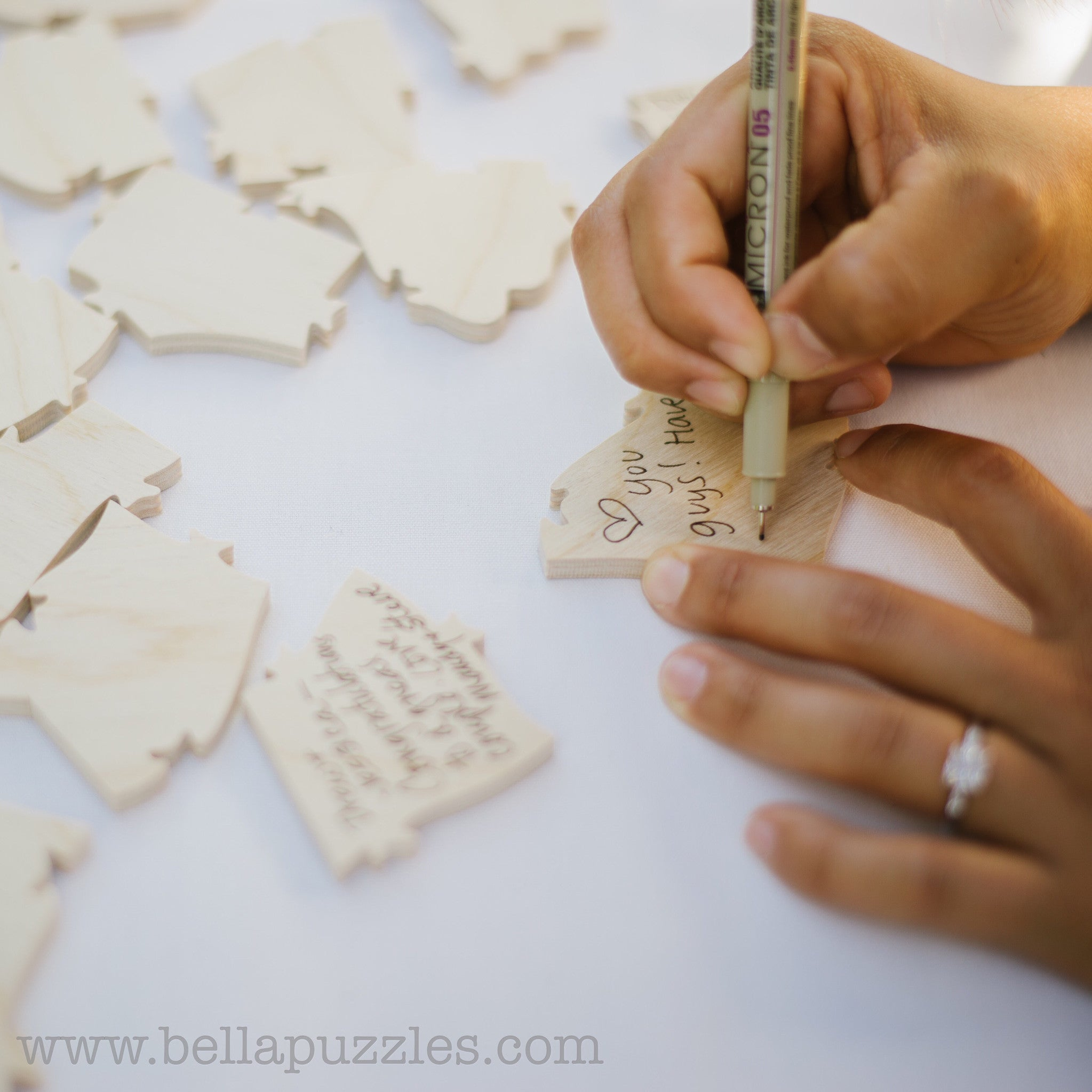 Woman signing a puzzle piece from a wooden guestbook puzzle made by BELLA PUZZLES. Guestbook puzzles are growing very popular for weddings, mitzvahs, showers, and other occasions. Made by BELLA PUZZLES.