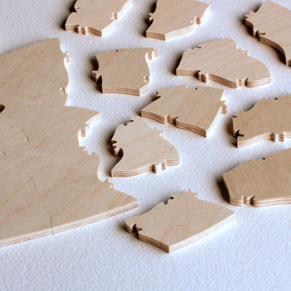 Wooden jigsaw puzzles pieces, plain wood on a white tabletop, from a BELLA PUZZLES wedding puzzle guestbook. Puzzle pieces are about 2 x 2 inches. You can order extra pieces in increments of five pieces from BELLA PUZZLES for any of our puzzle styles.