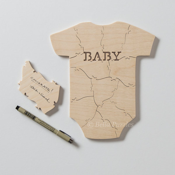 wooden jigsaw puzzle guestbook for baby shower in shape of baby garment with word BABY on chest, with signed puzzle piece and pen