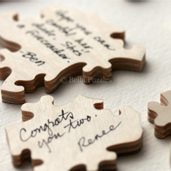 close up of signed wooden guestbook puzzle pieces