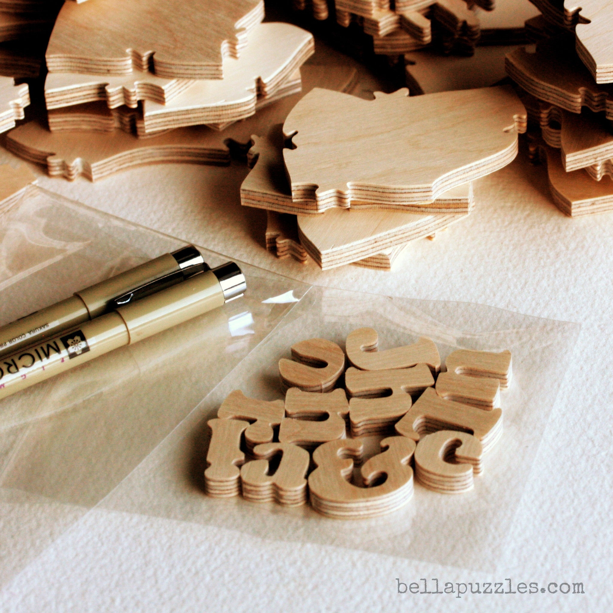 Handcrafted wooden puzzle pieces, pens, and letter-shaped pieces from a Bella Puzzle. A wedding guestbook alternative.