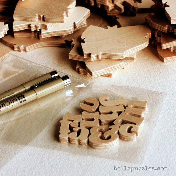 Handcrafted wooden puzzle pieces, pens, and letter-shaped pieces from a wedding guestbook puzzle. A unique guestbook alternative made by BELLA PUZZLES.
