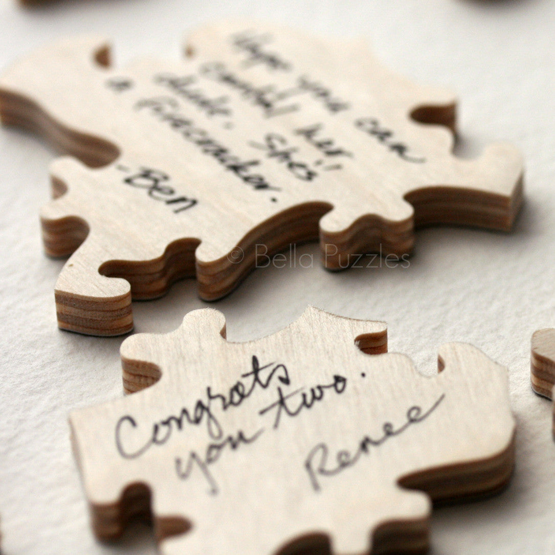 Signed pieces from a custom wooden puzzle wedding guestbook, by Bella Puzzles.